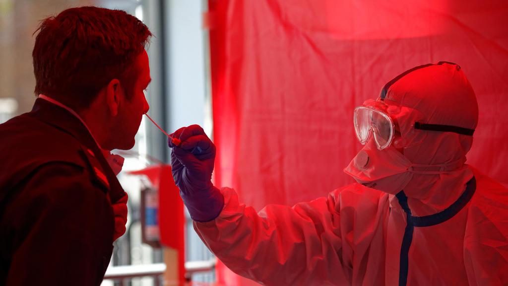 31.03.2020, Nordrhein-Westfalen, Köln: Einem Mitarbeiter der Berufsfeuerwehr Köln wird im dritten Infektionsschutzzentrum der Stadt Köln mit einem Stäbchen ein Abstrich für einen Test auf den Coronavirus entnommen. In der neu eröffneten Einrichtung i