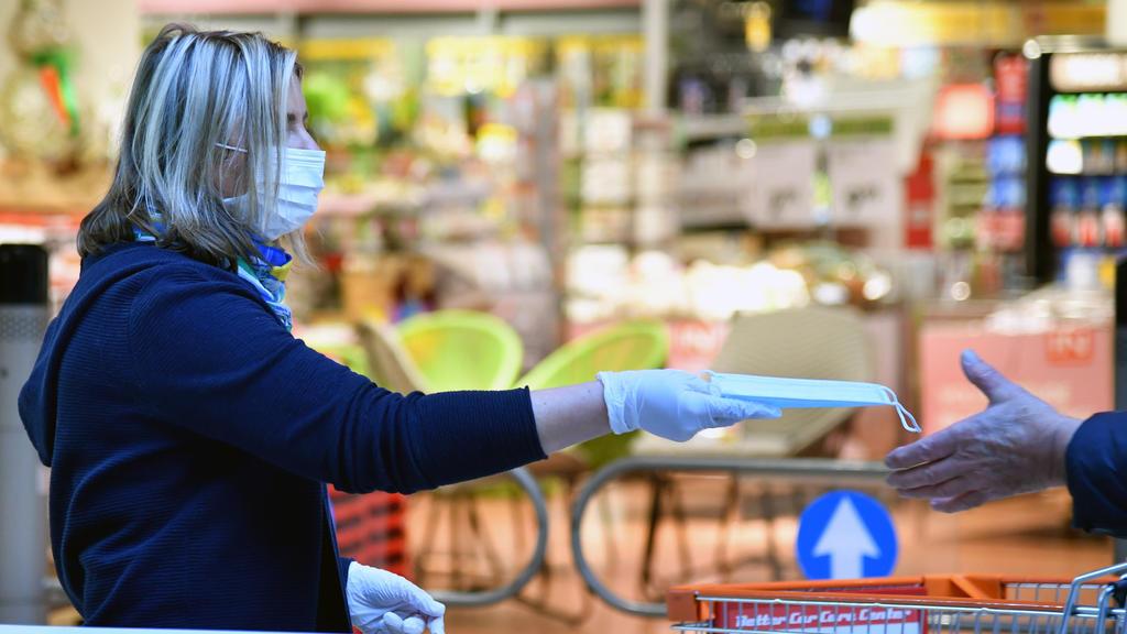 01.04.2020, Österreich, Salzburg: Die Mitarbeiterin eines Interspars verteilt am Eingang des Supermarktes Mundschutzmasken an Kunden. Ab dem Zeitpunkt der Aushändigung sei das Tragen während des Einkaufs Pflicht, wie der österreichische Bundeskanzler