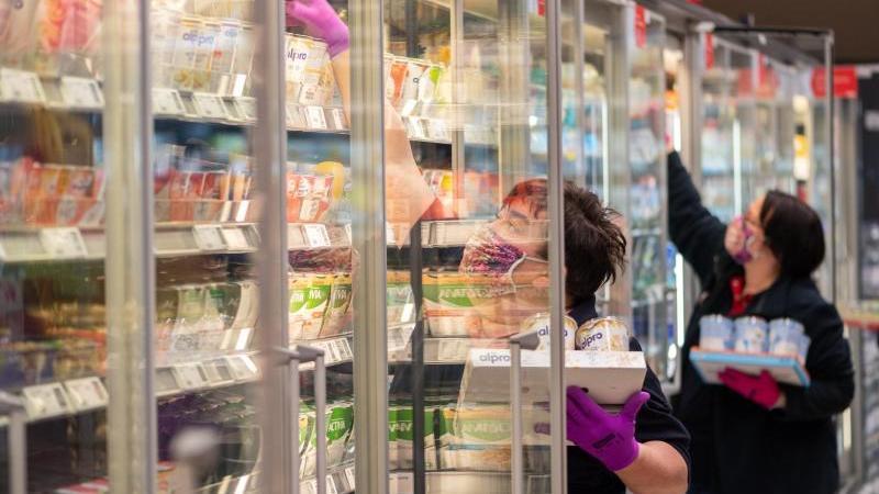 Mitarbeiterinnen in einem Supermarkt tragen Schutzmasken, während sie vor der Ladenöffnung die Regale mit Waren bestücken. Foto: Robert Michael/dpa/Archivbild