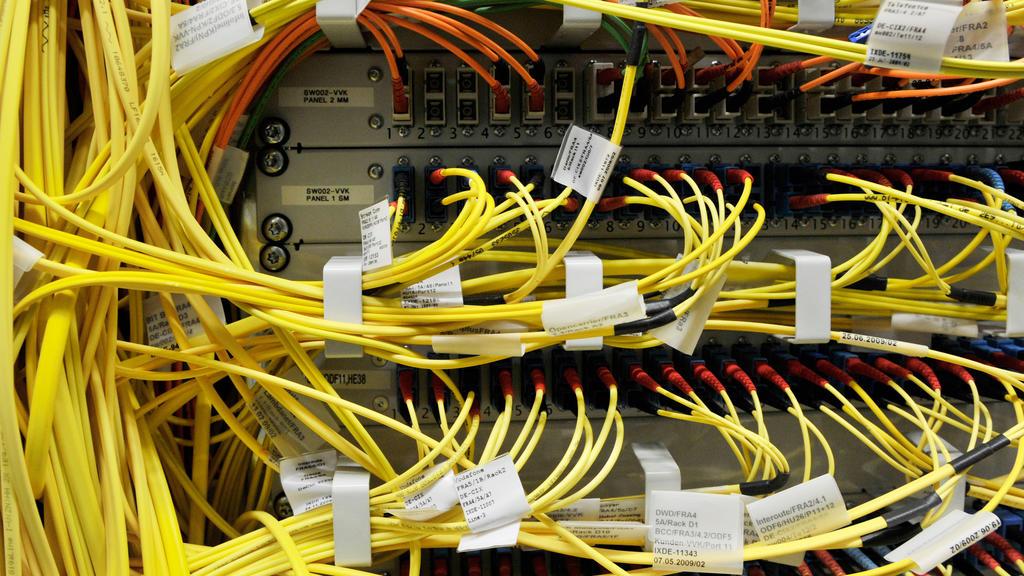 ARCHIV - 26.04.2010, Hessen, Frankfurt Am Main: Etliche Terrabyte an Daten laufen durch die gelben Glasfaserleitungen der Firma De-Cix. Der in Frankfurt basierte weltgrößte Internet-Knoten DE-CIX hatte mitgeteilt, der durchschnittliche Datenverkehr h