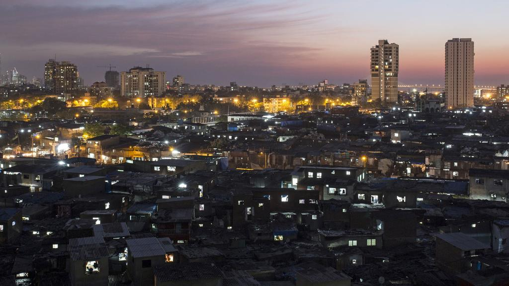 FILE PHOTO: High-rise residential towers are seen behind shanties in Dharavi, one of Asia's largest slums, in Mumbai March 18, 2015. REUTERS/Danish Siddiqui/File Photo