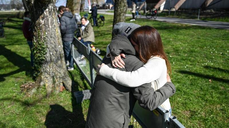 Andy aus Deutschland und Olivia aus der Schweiz umarmen sich an der Deutsch-Schweizer Grenze. Foto: Felix Kästle/dpa