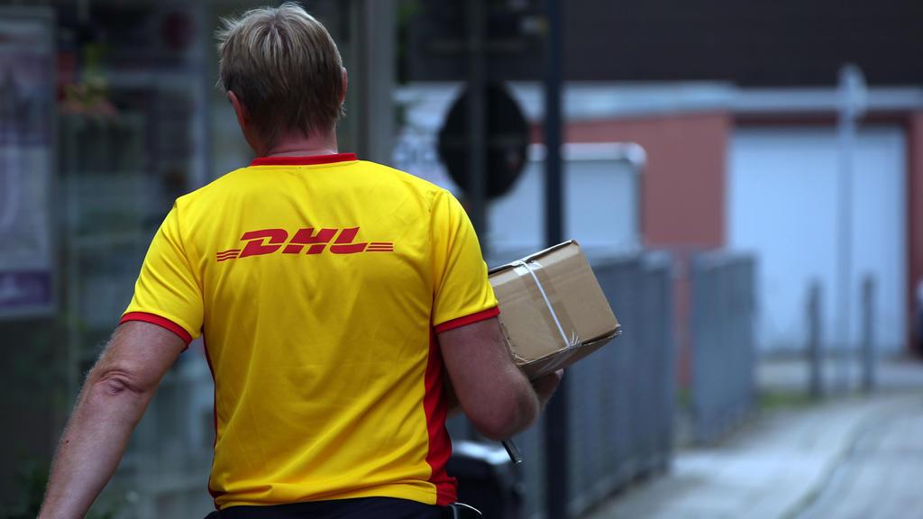 ARCHIV - 02.09.2015, Nordrhein-Westfalen, Herten: Ein Paketzustellerder von Deutsche Post DHL liefert ein Paket aus. (Zu dpa «Deutsche Post bereitet Einschränkungen wegen Corona-Pandemie vor») Foto: picture alliance / dpa +++ dpa-Bildfunk +++