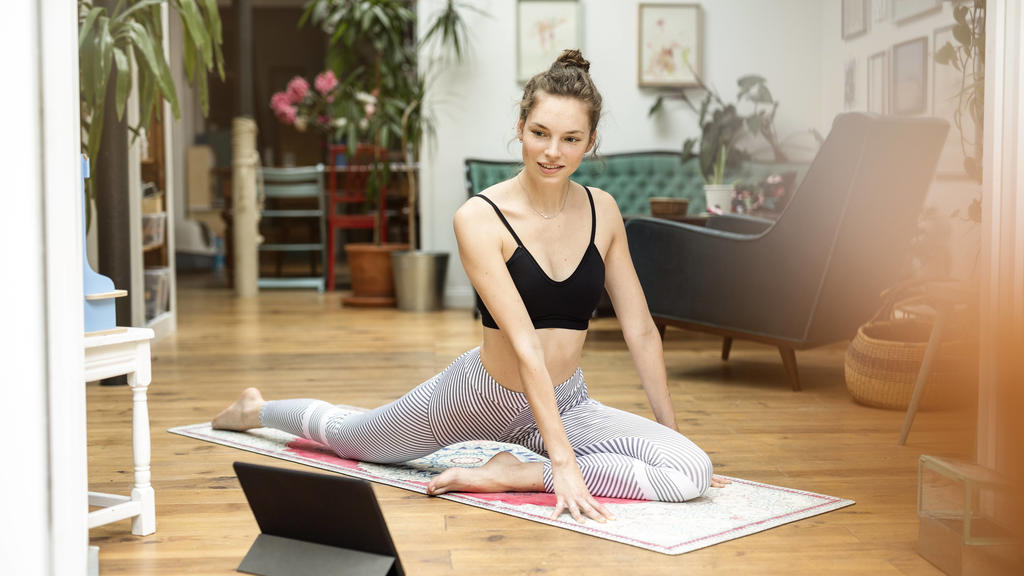 Young woman practicing yoga at home, using yoga app on digital tablet model released Symbolfoto property released PUBLICATIONxINxGERxSUIxAUTxHUNxONLY PESF01776