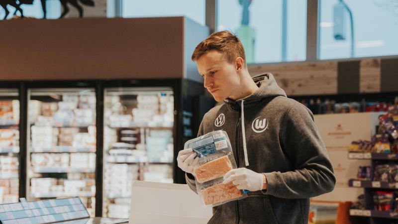 Yannick Gerhardt, Spieler des VfL Wolfsburg, hilft beim Einräumen der Ware in einem Supermarkt. Foto: -/VfL Wolfsburg/dpa
