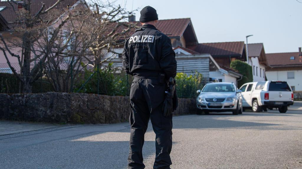 03.04.2020, Bayern, Vogtareuth: Ein Polizist steht auf einer Straße vor einem Haus in Vogtareuth, in dem drei Tote Menschen aufgefunden worden waren. Zwei tote Kinder und ihre tote Mutter haben Ermittler in einem Haus in Vogtareuth nahe Rosenheim gef