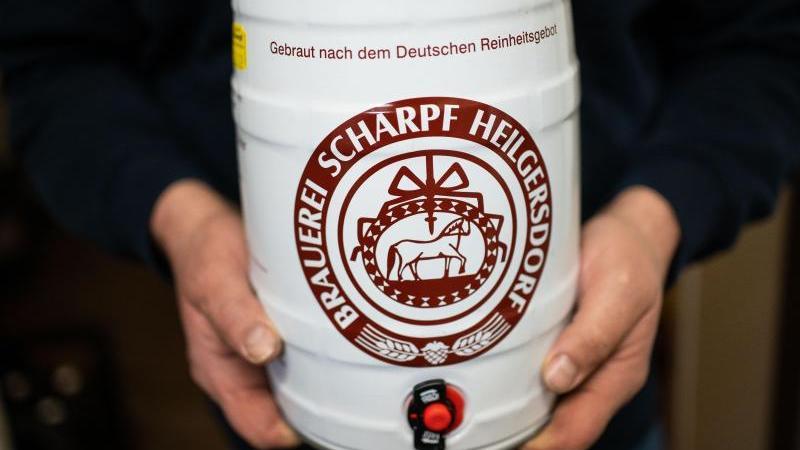 Werner Scharpf hält ein Bierfaß mit dem Logo der Brauerei in den Händen. Foto: Nicolas Armer/dpa