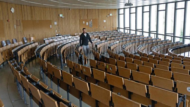 Der Leiter des Hausdienstes Ingo Voigt geht durch die Stuhlreihen eines Vorlesungssaales der Universität Hildesheim. Foto: Insa Lange/Universität Hildesheim/dpa