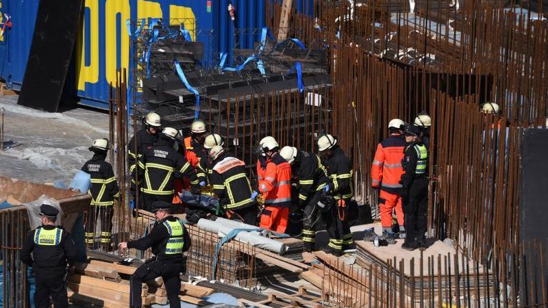 Einsatzkräfte versorgen auf einer Baustelle in der HafenCity einen verletzten Arbeiter. Foto: Daniel Bockwoldt/dpa