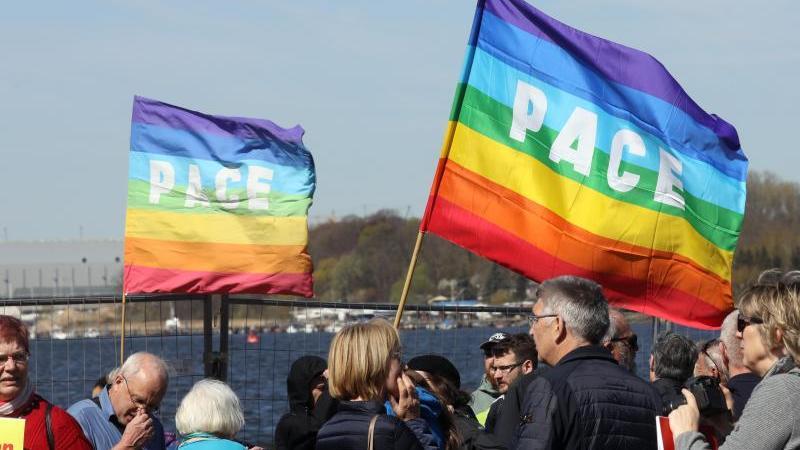 Teilnehmer an einem Ostermarch halten Fahnen der internationalen Friedensbewegung in die Höhe. Foto: Bernd Wüstneck/dpa-Zentralbild/ZB/Symbolbild