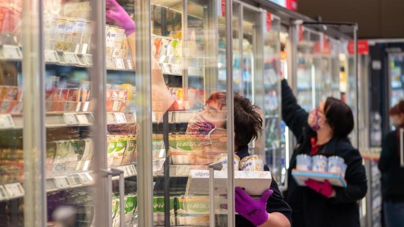 Mitarbeiterinnen in einem Supermarkt tragen Schutzmasken, während sie die Kühlregale mit Waren bestücken. Foto: Robert Michael/dpa-Zentralbild/dpa