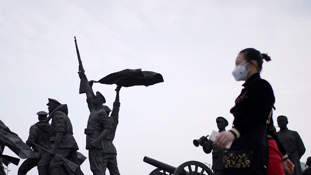 A resident wearing a face mask walks past statue symbolising Xinhai Revolution, a revolution that toppled China's last emperor in 1911, in Wuhan, Hubei province, the epicentre of China's coronavirus disease (COVID-19) outbreak, April 6, 2020. REUTERS