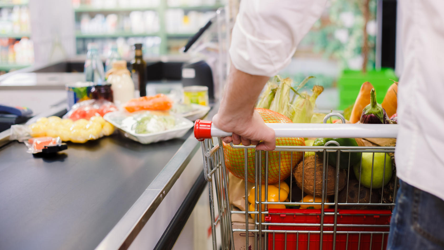 Ein Mann steht an der Supermarkt-Kasse.