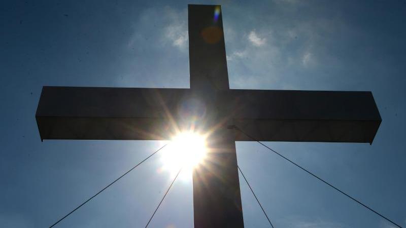 Ein Kreuz unter blauem Himmel. Foto: Marcus Brandt/dpa/Symbolbild