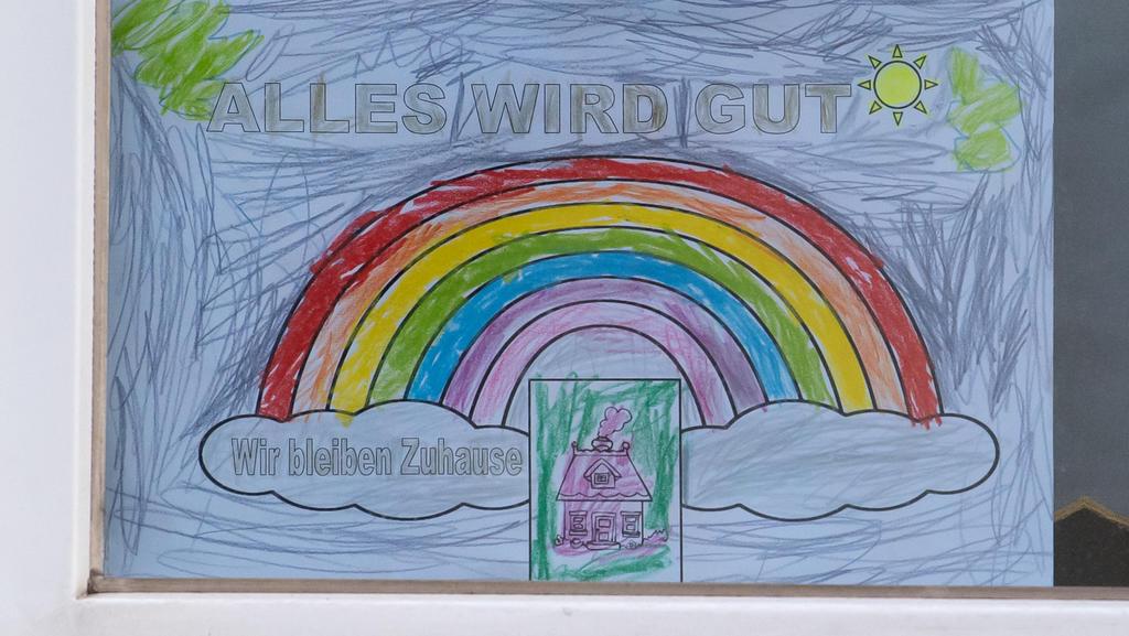 """26.03.2020, Bayern, München: Ein DIN A4 großes Blatt Papier mit einem Regenbogen und der Aufschrift """"Alles wird Gut - Wir bleiben Zuhause"""" hängt in einem Fenster zur Strassenseite. Foto: Sven Hoppe/dpa +++ dpa-Bildfunk +++"""