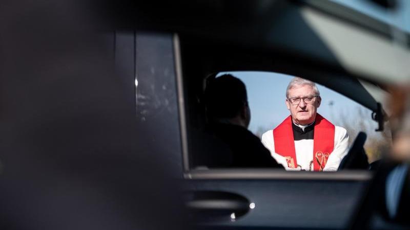 Stadtdechant Pfarrer Frank Heidkamp spricht mit Besuchern des Gottesdienstes im Auto. Foto: Fabian Strauch/dpa