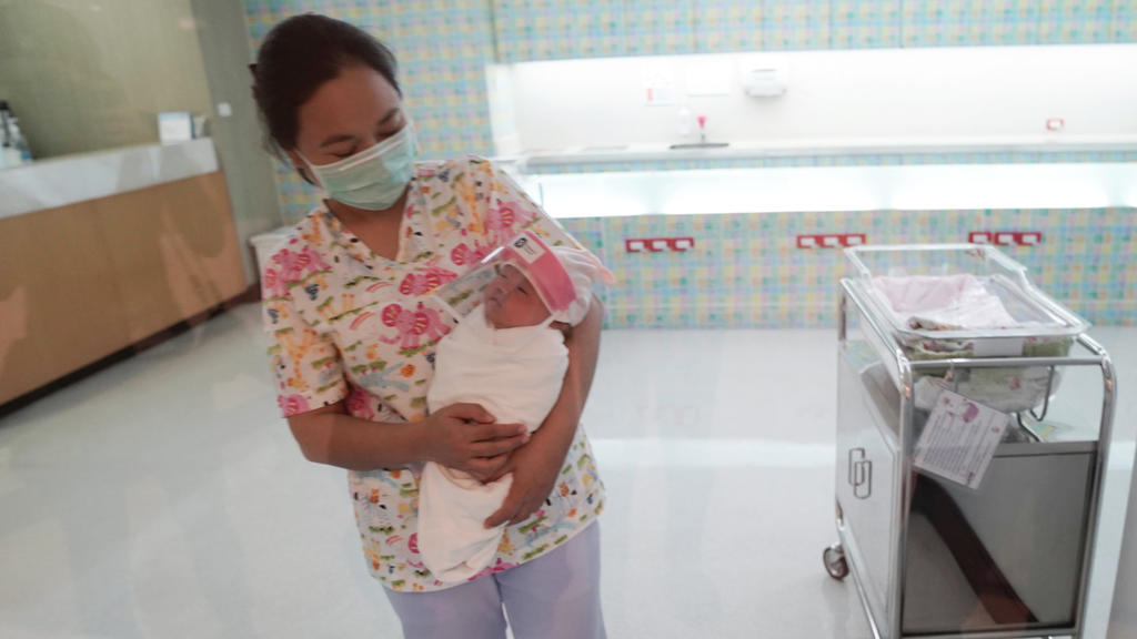 A nurse wearing a protective face mask holds a newborn baby wearing a protective face shield during the coronavirus disease (COVID-19) outbreak at the Praram 9 hospital in Bangkok, Thailand, April 9, 2020. REUTERS/Athit Perawongmetha