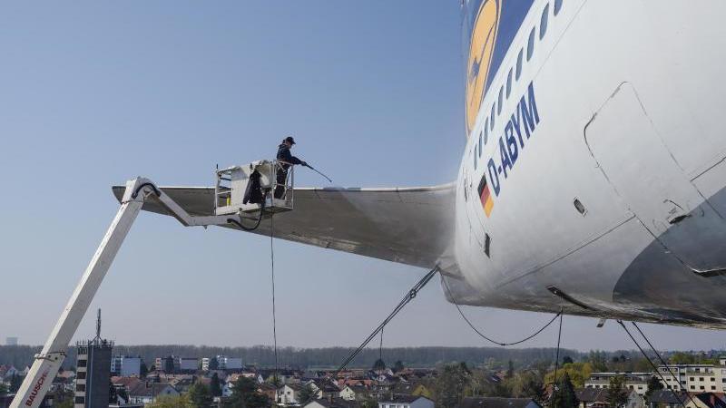 Eine Reinigungskraft säubert im Technikmuseum den Heckflügel einer ehemaligen Boeing 747-230 der Lufthansa. Foto: Uwe Anspach/dpa/Archivbild