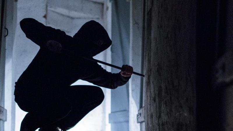 Ein Einbrecher benutzt ein Brecheisen, um eine Tür zu öffnen. Foto: Silas Stein/dpa/Symbolbild