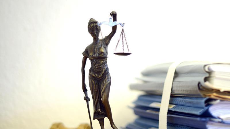 Eine modellhafte Nachbildung der Justitia steht neben Akten und einem Richterhammer auf einem Tisch. Foto: Volker Hartmann/dpa/Archivbild