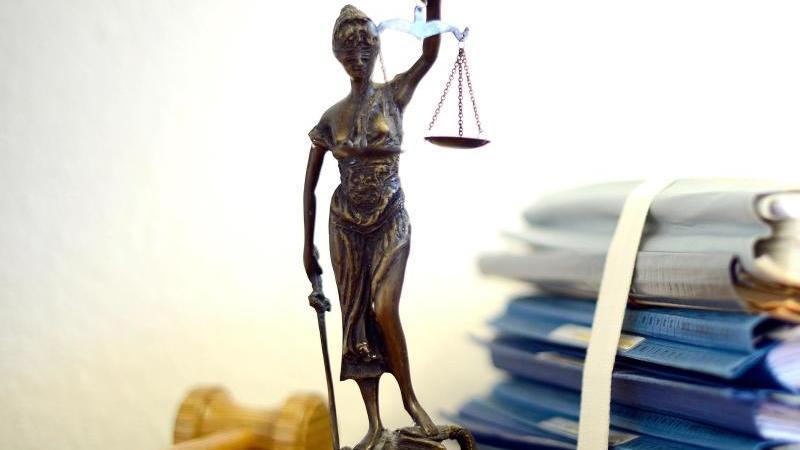 Die Justitia steht neben Akten und einem Holzhammer. Foto: Volker Hartmann/dpa/Archivbild