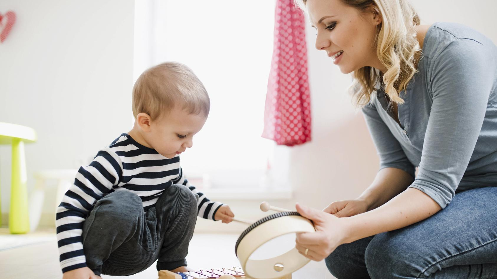 Mother and toddler son playing with musical instruments at home model released Symbolfoto property r
