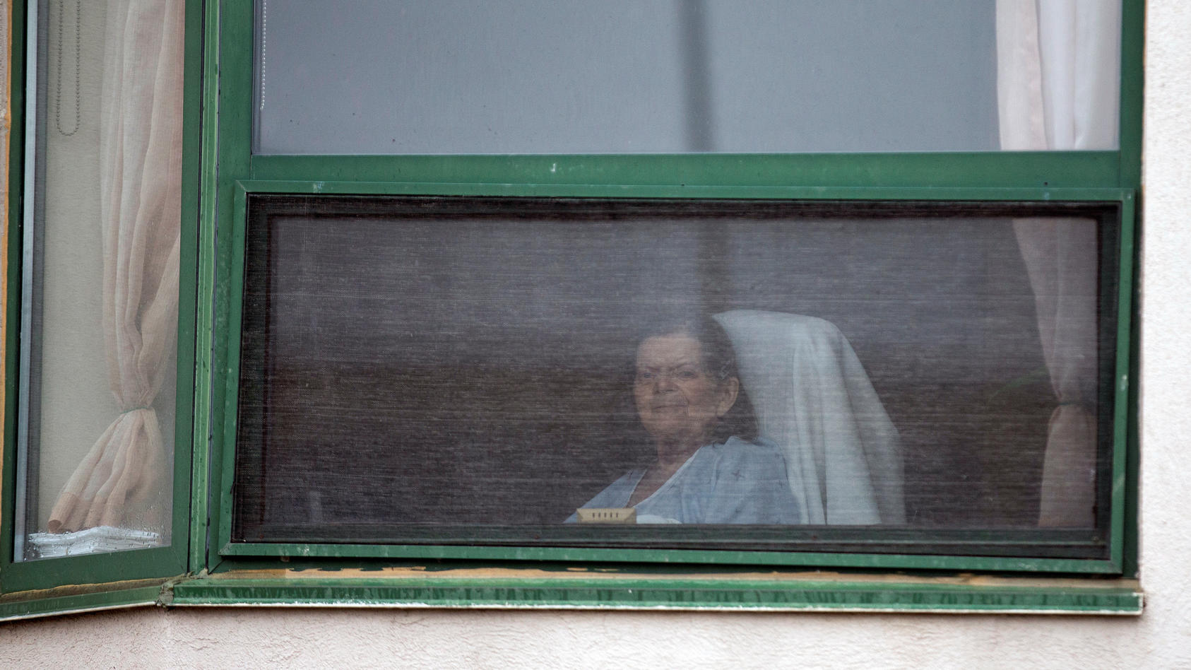 A resident looks out her window at a senior's long-term care facility during the coronavirus disease (COVID-19) outbreak, in Montreal