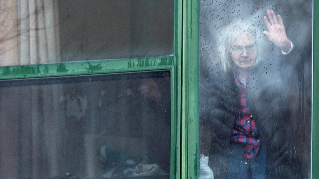 A resident waves from her window at Residence Herron, a senior's long-term care facility, following a number of deaths since the coronavirus disease (COVID-19) outbreak, in the suburb of Dorval in Montreal Quebec, Canada, April 13, 2020.  REUTERS/Chr