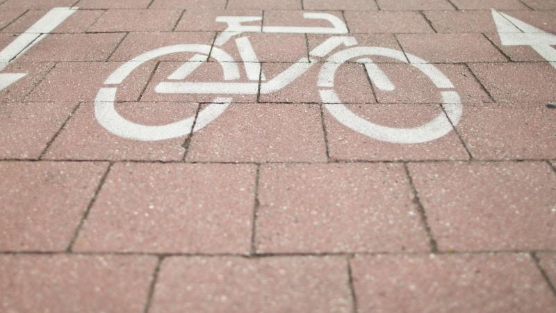 Ein Fahrradsymbol mit zwei wegweisenden Pfeilen auf dem Boden. Foto: picture alliance / dpa / Archivbild