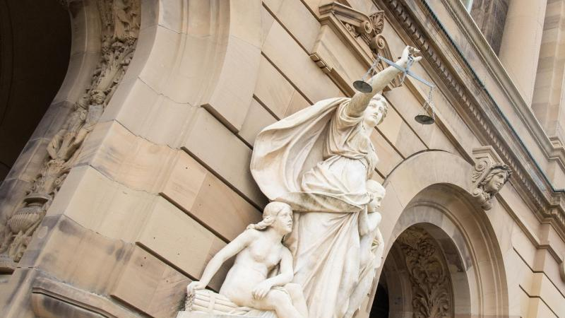 Vor eine Gerichtsgebäude hält eine Statue der Justitia eine Waagschale. Foto: Stefan Puchner/dpa/Symbolbild