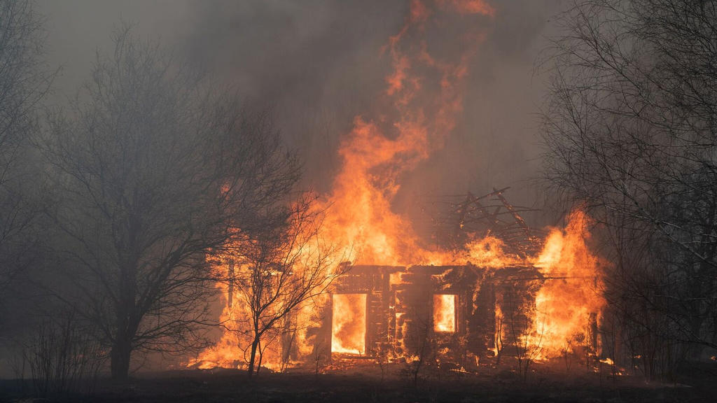 A view shows a wooden house on fire, as an operation to extinguish wildfires around the defunct Chernobyl nuclear plant continues, in Lyudvynivka in Kiev Region, Ukraine April 18, 2020. Picture taken April 18, 2020. REUTERS/Volodymyr Shuvayev