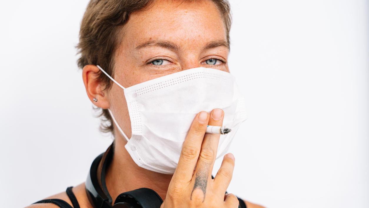 Rauchende Frau mit Schutzmaske und Zigarette