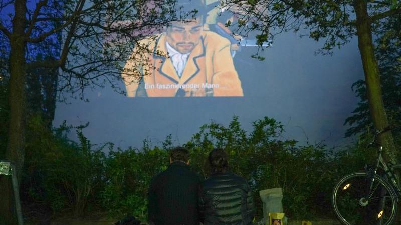 Ein Paar sieht sich auf der gegenüberliegenden Fassade einen Film an. Foto: Jörg Carstensen/dpa
