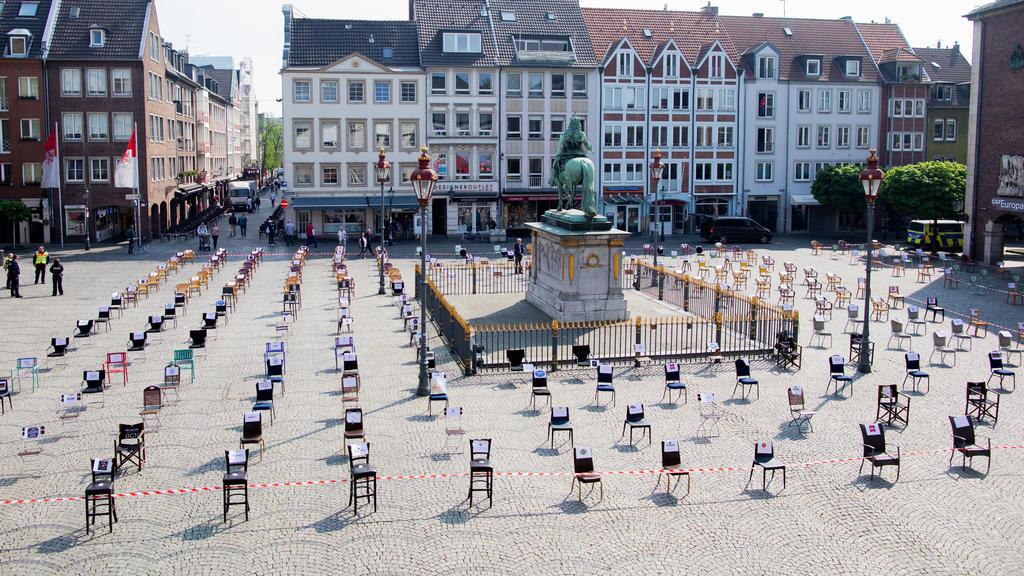 24.04.2020, Nordrhein-Westfalen, Düsseldorf: Leere Stühle stehen vor dem Rathaus und umgeben das Jan-Wellem-Denkmal. Düsseldorfer Gastronomen wollen hier mit einer Mahnwache auf ihre wirtschaftlichen Probleme aufmerksam machen. Foto: Rolf Vennenbernd