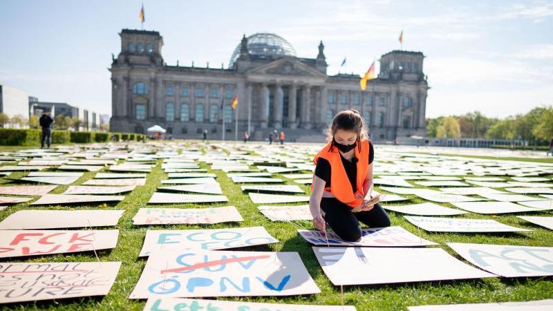 Luisa Neubauer legt Protestplakate für den Klimaschutz auf der Reichstagswiese aus. Foto: Kay Nietfeld/dpa