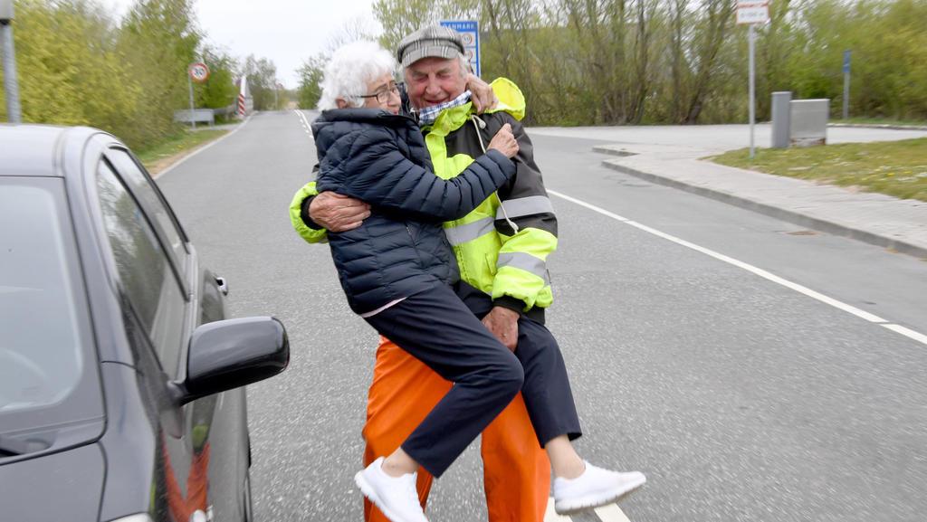 24.04.2020, Schleswig-Holstein, Aventoft: Inga Rasmussen aus Dänemark (85) wird von Karsten Tüchsen Hansen (89) aus Nordfriesland bei ihrem täglchen Treffen an der deutsch-dänischen Grenze hochgehoben. Nach Schließung der Grenze am 14.03.2020 hatten