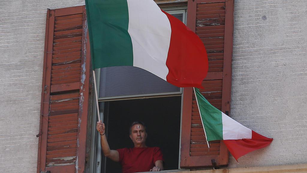 25.04.2020, Italien, Rom: Ein Mann schwenkt am Tag der Befreiung Italiens von seiner Wohnungen aus die italienische Fahne. Die üblichen Märsche in Gedenken an die Befreiung von den Deutschen Besatzern im Zweiten Weltkrieg, können während der Corona-P