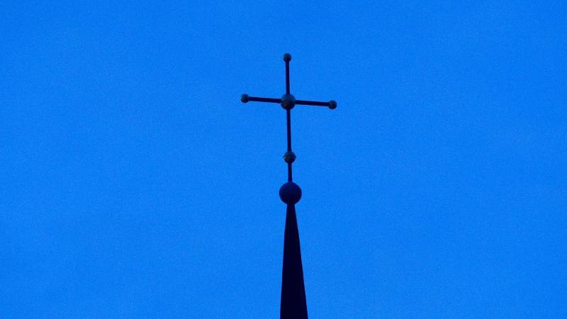 Ein Kreuz ist auf einer Kirchturmspitze zu sehen. Foto: Friso Gentsch/dpa/Symbolbild