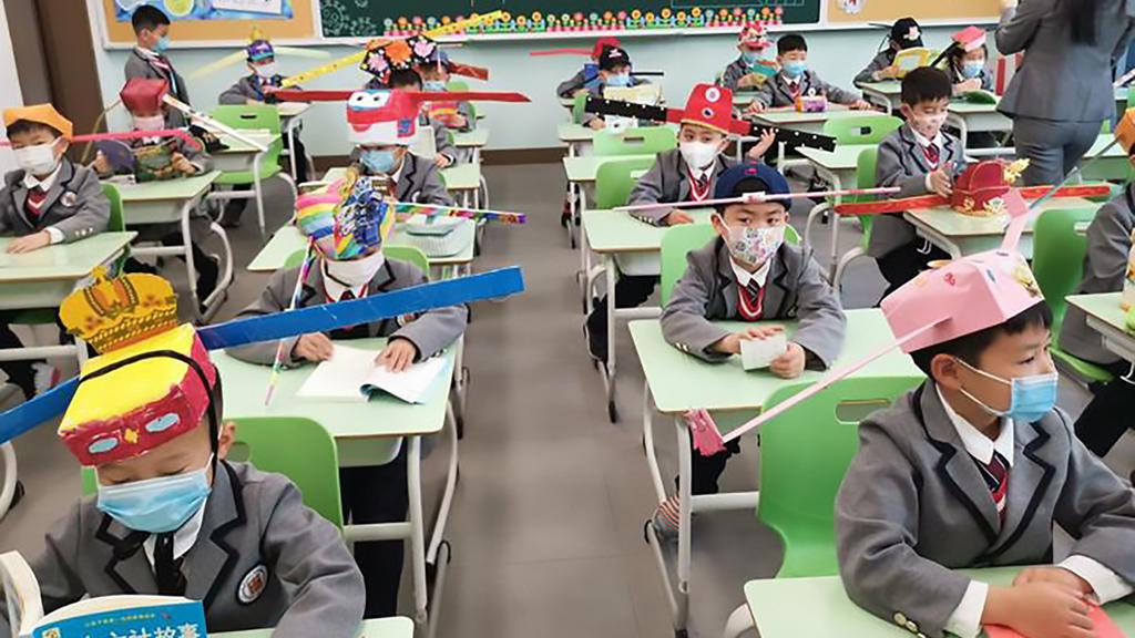 """Chinesischer Kinder mit """"Ein-Meter-Hüten"""" in der Schule"""