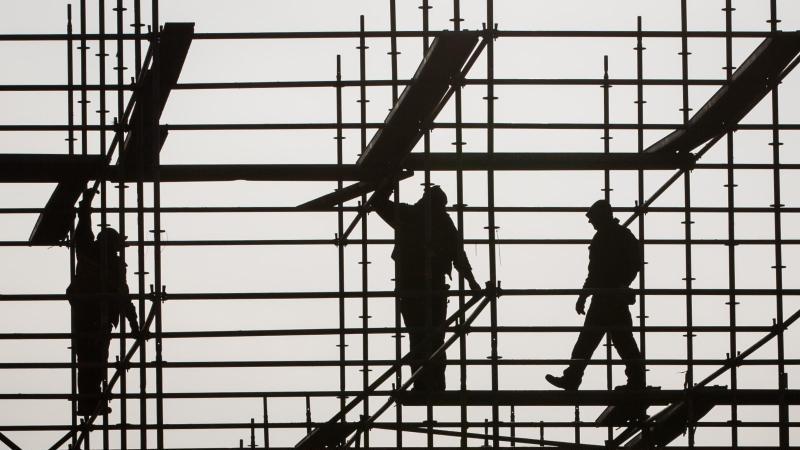 Gerüstbauer errichten in Hamburg auf einer Brückenbaustelle in der Hafencity ein Gerüst. Foto: Christian Charisius/dpa/Symbolbild