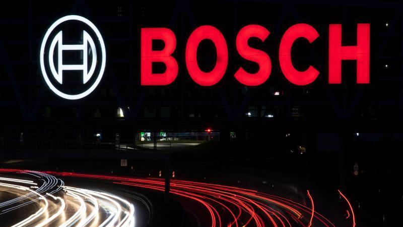 Das Logo des Technologiekonzerns Bosch leuchtet über einem Parkhaus. Foto: Marijan Murat/dpa