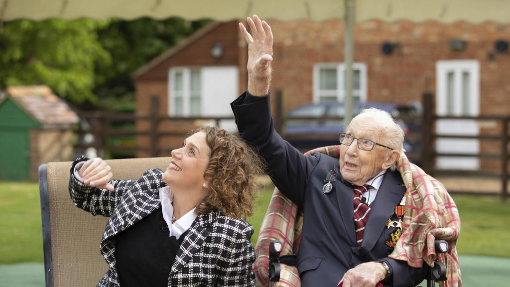 In this photo issued by Capture the Light Photography, showing Second World War veteran Captain Tom Moore with his daughter Hannah, as they react to Battle of Britain Memorial Flight flypast of a Spitfire and a Hurricane passing over his home as he c