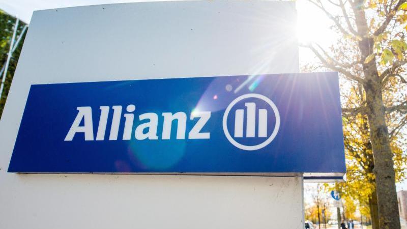 Ein Schild vor einem Gebäude der Allianz mit dem Logo des Versichungskonzerns steht im Gegenlicht der Sonne neben einem Baum. Foto: Marc Müller/dpa/Archivbild