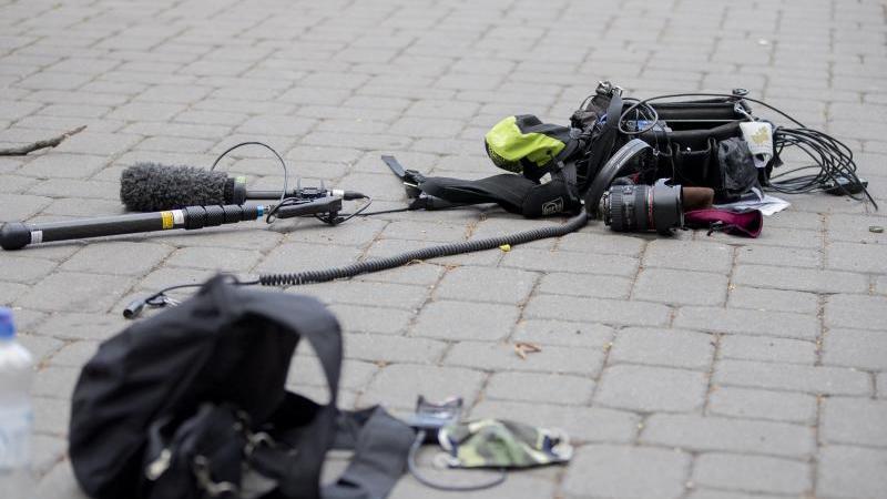Kamera-Ausrüstung liegt nach einem Übergriff auf dem Boden. Foto: Christoph Soeder/dpa