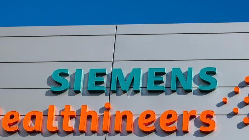 Logos und Schriftzüge am Hauptquartier des Medizintechnikkonzerns Siemens Healthineers. Foto: Daniel Karmann/dpa/Archivbild