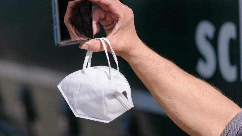 Eine Person hält eine Atemschutzmaske in der Hand. Foto: Ole Spata/dpa