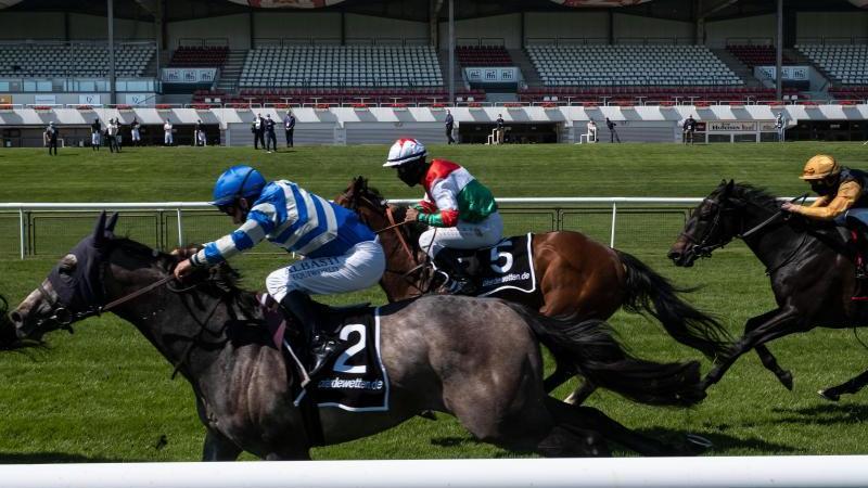 Vor leerer Tribüne reiten die Jockeys mit ihren Pferden auf der Rennbahn Neue Bult. Foto: Peter Steffen/dpa