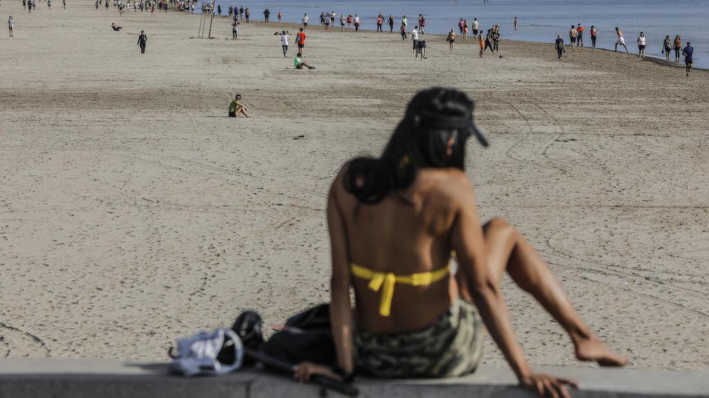 02.05.2020, Spanien, Valencia (comunidad Valenciana): Eine Frau sitzt in ihrem Bikini am Strand von Malvarrosa. Ab diesem Wochenende dürfen die Bürger im von der Corona-Pandemie schwer betroffenen Spanien erstmals nach sieben Wochen wieder im Freien