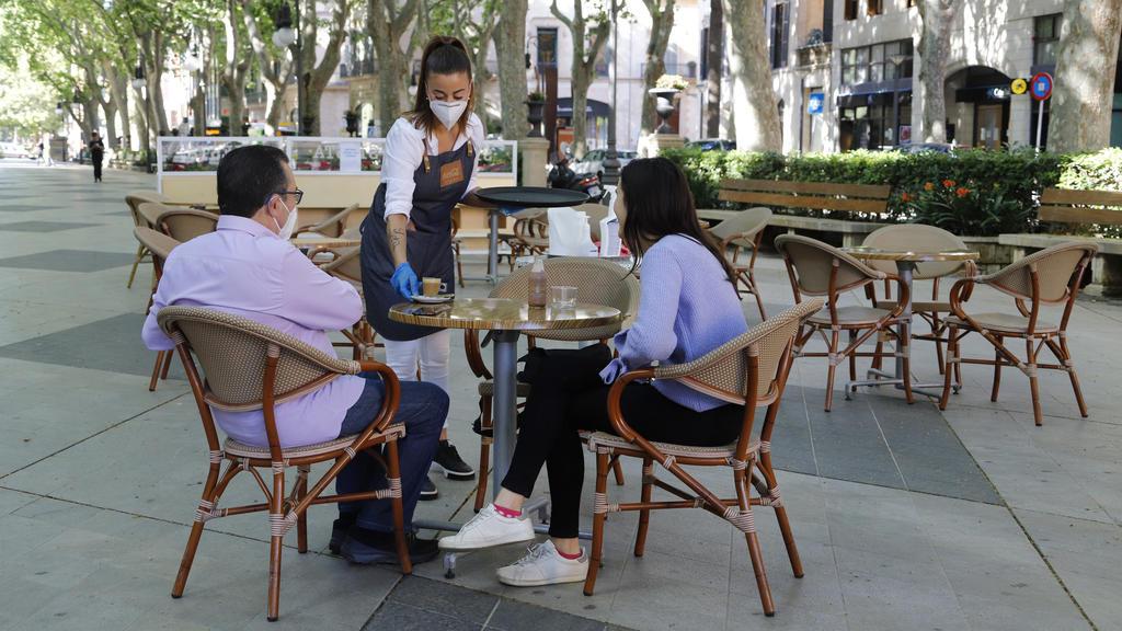 11.05.2020, Spanien, Palma: Am Tag der Wiedereröffnung serviert eine Kellnerin zwei Gästen auf der Terrasse einer Bar in Palma einen Kaffee. Ab Montag dürfen in der «Phase 1» der Lockerungen der Corona-Maßnahmen unter anderem Bars, Restaurants, Gesch