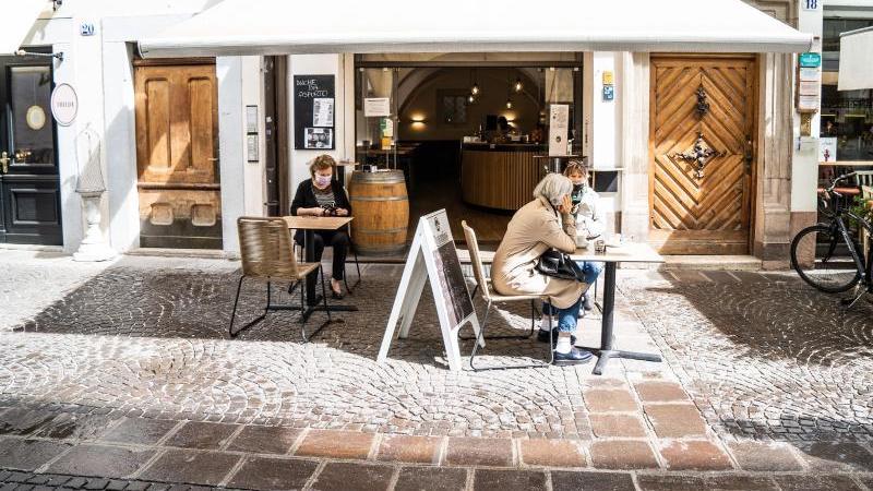 Frauen mit Mundschutz trinken Kaffee vor einer Bar in Bozen. Foto: Matteo Groppo/LaPresse via ZUMA Press/dpa